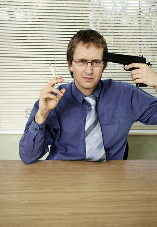 Bespectacled : Businessman pointing a gun at himself while smoking cigarette
