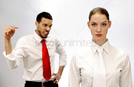 Conceptual : Businessman pointing angrily at his female colleague