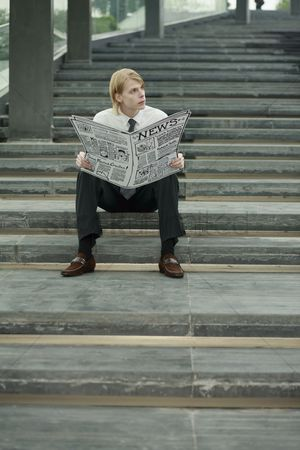 Cardboard cutout : Businessman reading newspaper on the stairs