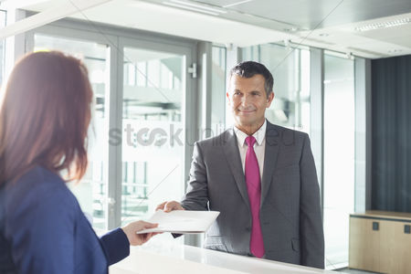 Notepad : Businessman receiving document from receptionist in office