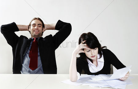 Relaxing : Businessman relaxing while his colleague is busy with her work