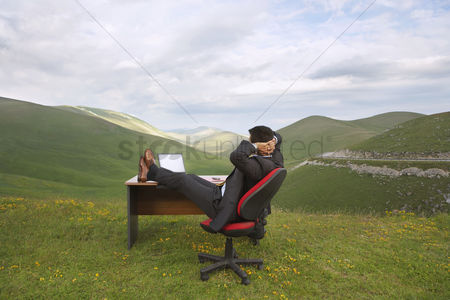 Satisfaction : Businessman relaxing with feet on desk in mountain field side view
