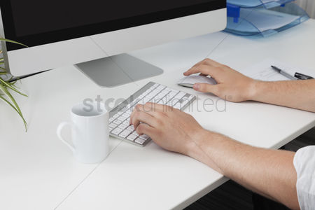 Businessmen : Businessman s hands using computer at desk