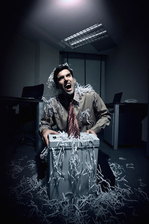 Paper shredder : Businessman shouting whiles his tie getting caught in a paper shredder