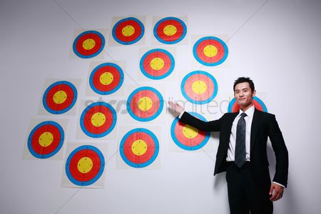 Motivation business : Businessman showing a wall of targets