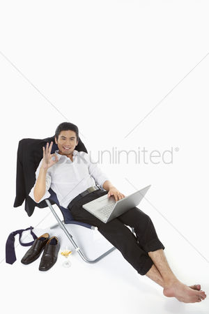 Portability : Businessman showing hand gesture while using laptop