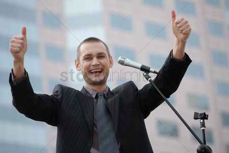 Gesturing : Businessman showing thumbs up while giving speech