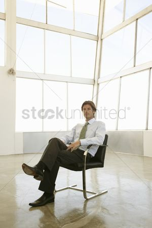 High ceiling : Businessman sits in  sunlit office with knees crossed