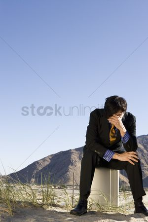 Loss : Businessman sitting on briefcase in the desert
