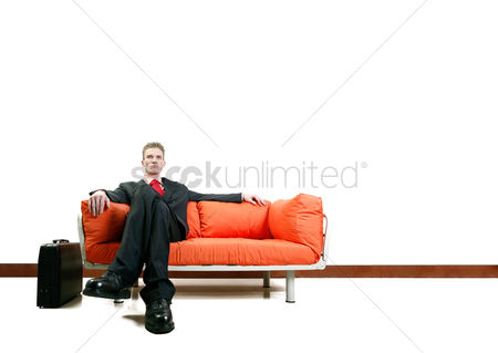 Relaxing : Businessman sitting on the couch with his legs crossed