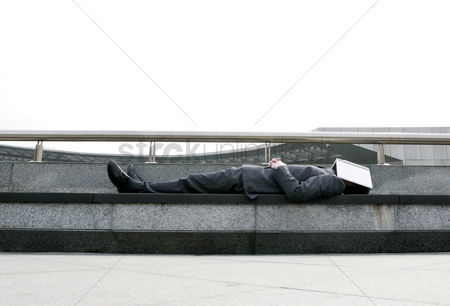 Employment issue : Businessman sleeping on the bench with a book covering his face