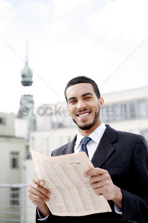 Determined : Businessman smiling while holding a newspaper