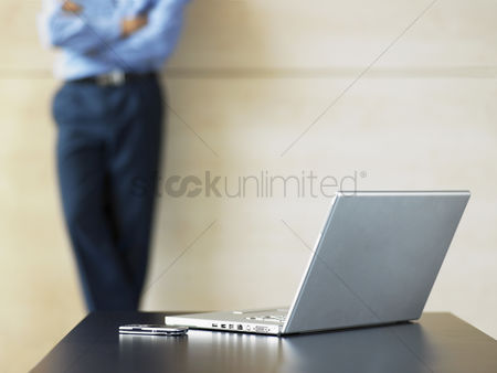 Cell phone : Businessman standing by laptop and cell phone on desk focus on foreground