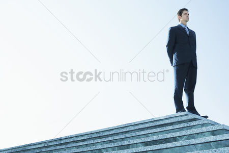 Steps : Businessman standing on marble platform low angle view