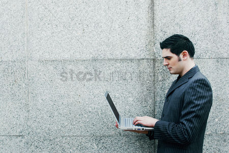 Resting : Businessman standing while using laptop
