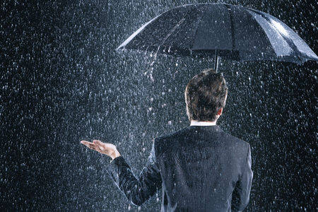 Black background : Businessman staying dry under umbrella during downpour back view