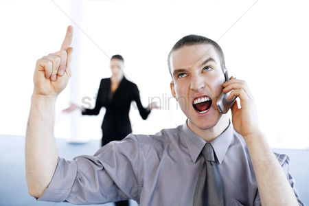 Sales person : Businessman talking angrily on the mobile phone