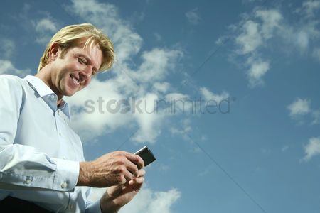 Smile : Businessman text messaging on the mobile phone