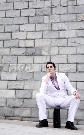 Wondering : Businessman thinking while sitting on briefcase
