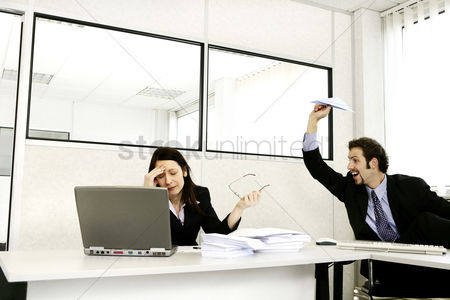 Employee : Businessman throwing a paper plane at his stressed up colleague