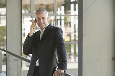 Business suit : Businessman using cell phone in office
