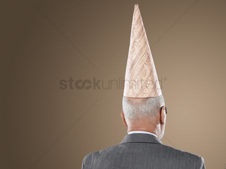 Ignorance : Businessman wearing dunce hat back view head and shoulders