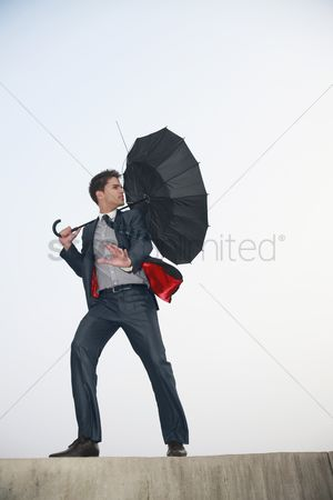 Blowing : Businessman with an umbrella  wind blowing his umbrella away