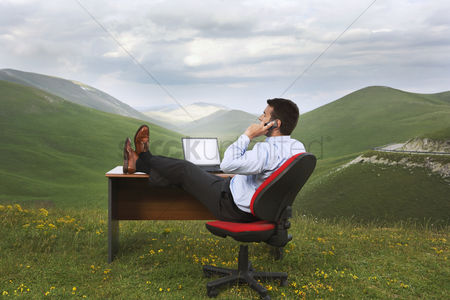 Furniture : Businessman with feet on desk in mountain field talking on phone side view