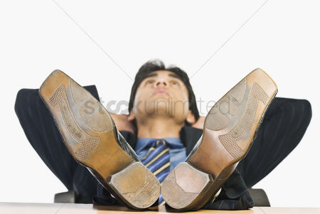 Corporation : Businessman with feet up on a desk
