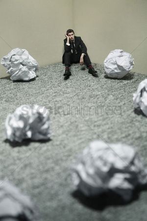 Worry : Businessman with giant sized crumpled papers on the floor