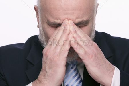 Head shot : Businessman with hands on head and eyes closed