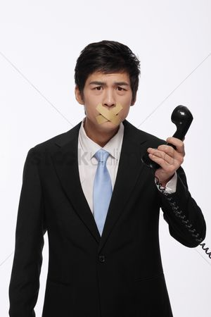 Forbidden : Businessman with his mouth taped  holding a telephone receiver