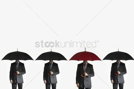 Business suit : Businessmen holding umbrellas standing side by side one red umbrella