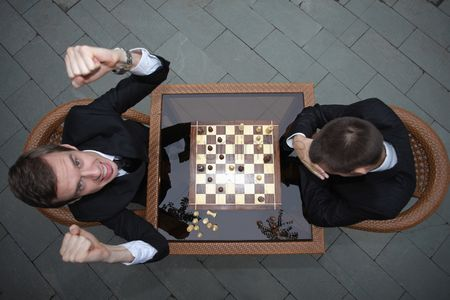 Loss : Businessmen playing chess outdoors  businessman cheering and raising fists