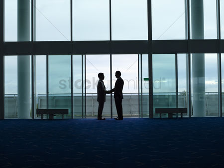Business suit : Businessmen shaking hands in doorway silhouette profile
