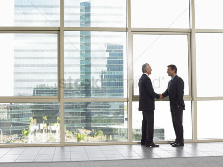 Satisfaction : Businessmen shaking hands in office building