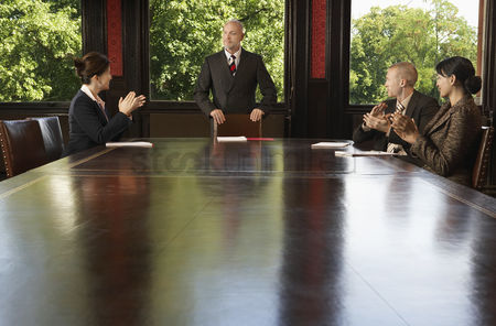 Leadership : Businesspeople around boardroom table applauding man
