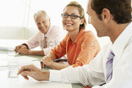 People : Businesspeople in conference meeting smiling