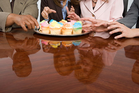 Interior : Businesspeople reaching for cupcakes