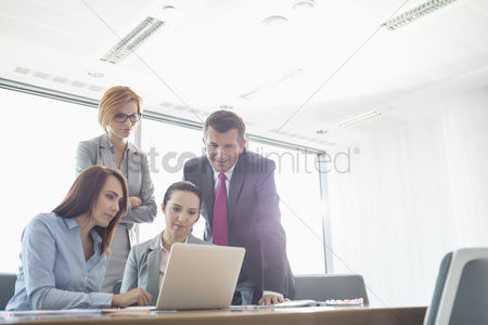 Businesswomen : Businesspeople using laptop in conference room