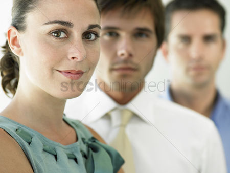 Leadership : Businesswoman and two businessmen focus on woman portrait