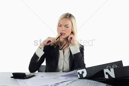 British ethnicity : Businesswoman biting her glasses while thinking