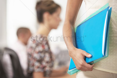 Interior background : Businesswoman carrying folder mid section close-up