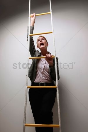 Motivation business : Businesswoman climbing rope ladder