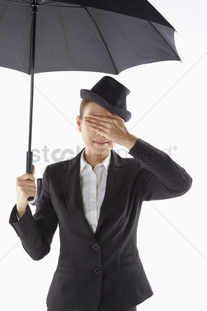 Ignorance : Businesswoman covering her eyes while standing under the umbrella