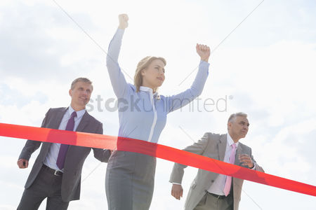 Celebrating : Businesswoman crossing finishing line with colleagues in background