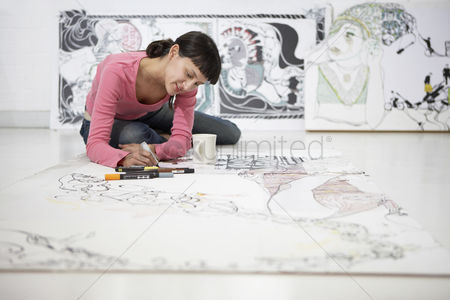 Creativity : Businesswoman drawing on large paper on floor
