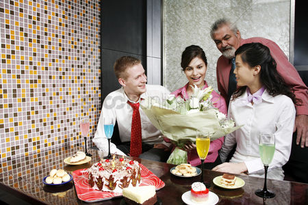 Celebrating : Businesswoman getting a bouquet of flowers for her birthday