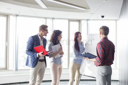 Businesswomen : Businesswoman giving presentation to colleagues in creative office