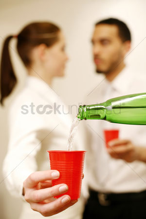 Wine bottle : Businesswoman having her drinks refilled while talking to her colleague
